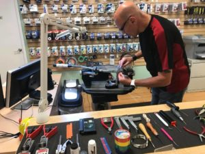 A racquet stringer stringing racquets in our Calgary store